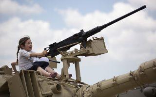 Παιχνίδι με τα όπλα. Ημέρα μνήμης για το Ισραήλ και τα νεκροταφεία γέμισαν κόσμο. Στο πλαίσιο των εορτασμών τα παιδιά είχαν την δυνατότητα να περιεργαστούν από κοντά πραγματικά όπλα και τανκ, όπως η πιτσιρίκα που το διασκεδάζει στην φωτογραφία και που το πολύ σε μια δεκαετία θα υπηρετεί και αυτή στον Ισραηλινό στρατό. AP Photo/Oded Balilty