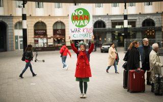 Διαδηλώτρια στις Βρυξέλλες λέει όχι στον πόλεμο με το Ιράν.