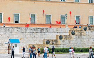 Τουρίστες με φόντο τις κόκκινες μπογιές στην πρόσοψη του Κοινοβουλίου.