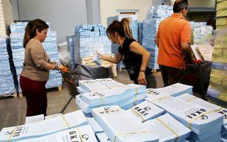 Υπάλληλοι της Περιφέρειας Αττικής ετοιμάζουν σάκους με ψηφοδέλτια.