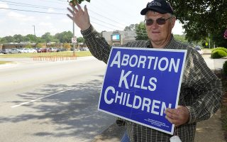 Jim Snively, of Huntsville, waves to passing cars while holding an anti-abortion sign in front of the Alabama Women's Wellness Center Friday, May 17, 2019 in Huntsville, Ala. The Alabama legislation signed into law Wednesday would make performing or attempting to perform an abortion at any stage of pregnancy a felony. The ban does not allow exceptions for rape and incest.(AP Photo/Eric Schultz)