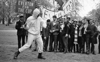 Οπαδοί του ποδοσφαιρικού κλαμπ της Έβερτον, οι οποίοι μετέβησαν στο Λονδίνο, για να παρακολουθήσουν την αναμέτρηση της αγαπημένης τους ομάδας με τη Σέφιλντ Γουένσντεϊ για τον τελικό του Κυπέλλου Αγγλίας (Football Association Cup) στις 14 Μαΐου στο Γουέμπλεϊ, παρακολουθούν εντυπωσιασμένοι τον Αμερικανό θρύλο της πυγμαχίας, Μοχάμεντ Άλι, να προπονείται στο Χάιντ Παρκ, το 1966. (AP Photo/Kemp)