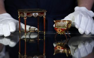 A rare and fine Faberge gold and enamel miniature bonbonniere chair, right, and a Faberge gold, guillochee enamel and nephrite table bonbonniere both by workmaster Michael Perchin from around 1900, on display during a press preview at Sotheby's auction house in London, Friday, May 31, 2019. Both items are expected to sell individually for some 800,000 to 1.2 million pounds sterling, (US$ 1-1.5 million) at auction on June 4. The miniature's are designed to hold little treats of sweets or chocolates. (AP Photo/Alastair Grant)