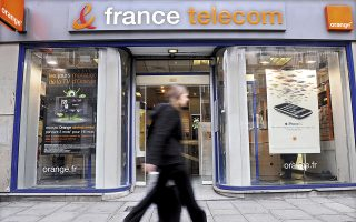 A pedestrian passes a France Telecom store in Paris, France, on Monday, Feb. 9, 2009. The company releases its earnings this week. France Telecom, Europe's third-largest phone company, said full-year profit fell 35 percent as it wrote down the value of goodwill and the tax bill increased..  Photographer: Antoine Antoniol/Bloomberg News