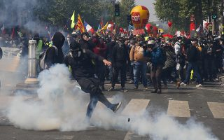 An activist kicks away a tear gas canister during a May Day demonstration in Paris, Wednesday, May 1, 2019. French authorities announced tight security measures for May Day demonstrations, with the interior minister saying there was a risk that