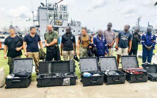 Οι τρεις Ελληνες και ο Αμερικανός που συνελήφθησαν μαζί με το πλήρωμα του «Sea Angel 3» πίσω από τον οπλισμό που κατασχέθηκε, στο λιμάνι του Λάγος.