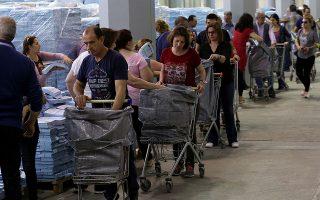 Υπάλληλοι γεμίζουν τα καρότσια με ψηφοδέλτια των συνδυασμών για να προωθηθούν στα εκλογικά τμήματα. EPA/ORESTIS PANAGIOTOU