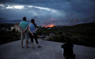 Αποσβολωμένοι πολίτες παρακολουθούν τις φλόγες να «κατασπαράσσουν» το Μάτι. Οπως αποδεικνύουν τα ηχητικά ντοκουμέντα, την ίδια ώρα θεατής ήταν και ο κρατικός μηχανισμός. Πυροσβέστες και εθελοντές έδωσαν σχεδόν αβοήθητοι τη μάχη για να σώσουν ζωές...