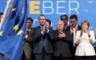 Manfred Weber, left, leading candidate of the EPP in the 2019 European elections, German Chancellor Angela Merkel, right, and former Polish President Lech Walesa, center, attend the joint closing rally of the EPP, CDU and CSU parties for European elections in Munich, Germany Friday May 24, 2019. (Sven Hoppe/dpa via AP)