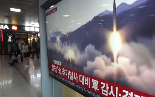 FILE - In this May 4, 2019 file photo, A TV screen shows file footage of North Korea's missile launch during a news program at the Seoul Railway Station in Seoul, South Korea. South Korea's military says North Korea has fired at least one unidentified projectile from its western area. It's the second such launch in the last five days. The signs read: