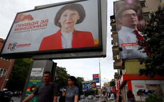 People walk past campaign billboard of the opposition candidate Gordana Siljanovska-Davkova and campaign banner of the ruling Social Democratic Union (SDSM) candidate Stevo PendarovskiΚfor presidential election on May 5 in Skopje, North Macedonia May 3, 2019. REUTERS/Ognen Teofilovski