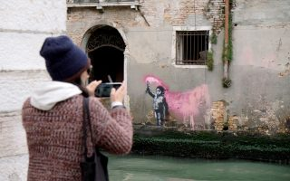 A woman takes a photo of the new mural by Banksy, on a building along the Rio de Ca Foscari canal in Venice, Italy May 15, 2019. Picture taken May 15, 2019. REUTERS/Manuel Silvestri