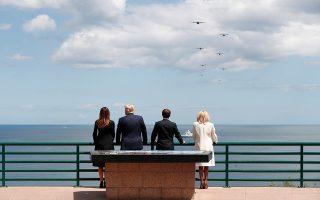 Συνοδευόμενοι από τις συζύγους τους, Τραμπ και Μακρόν ατενίζουν τα πολεμικά αεροπλάνα που πετούν πάνω από την Κολβίλ της Νορμανδίας.