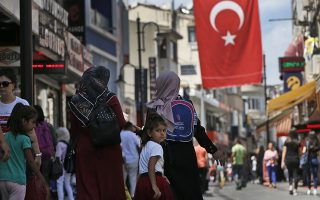 People walk at a market in Istanbul, Wednesday, Aug. 15, 2018. The Turkish lira currency has nosedived in value in the past week over concerns about Turkey's President Recep Tayyip Erdogan's economic policies and after the United States slapped sanctions on Turkey angered by the continued detention of an American pastor. (AP Photo/Lefteris Pitarakis)