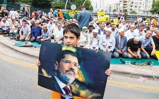 Ενα αγόρι κρατάει φωτογραφία του Μόρσι έξω από την πρεσβεία της Αιγύπτου στην Αγκυρα.