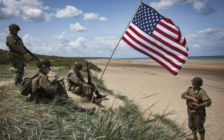 epaselect epa07623490 French history enthusiasts dressed as a US soldiers from WW2 sit by a US flag planted in a sand dune on Omaha Beach on the Normandy coast ahead of the 75th D-Day anniversary, in Colleville-sur-Mer, France, 03 June 2019. World leaders are to attend memorial events in Normandy, France on 06 June 2019 to mark the 75th anniversary of the D-Day landings, which marked the beginning of the end of World War II in Europe.  EPA/IAN LANGSDON