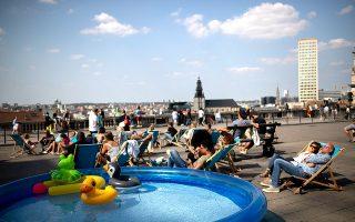 Απολαμβάνοντας τη λιακάδα στην πλατεία Poelaert. (Φωτογραφία: AP Photo/Francisco Seco)