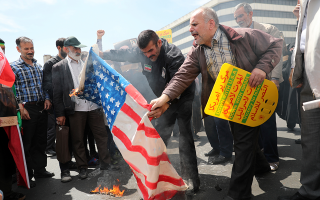 Ιρανοί πολίτες καίνε μία αμερικανική σημαία κατά τη διάρκεια μίας διαδήλωσης στην Τεχεράνη, λίγο μετά την προσευχή της Παρασκευής, στις 10 Μαΐου. (AP Photo/Ebrahim Noroozi)