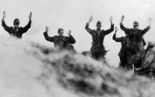 Γερμανοί στρατιώτες με σηκωμένα τα χέρια εμφανίζονται δειλά από την κορυφή ενός λόφου κατά την παράδοση τους στα προελαύνοντα αμερικανικά στρατεύματα, πέντε ημέρες μετά τη συμμαχική απόβαση στη Νορμανδία και τις πρώτες καθοριστικές μάχες για τον έλεγχο των νορμανδικών ακτών και τη δημιουργία προγεφυρωμάτων από τους Συμμάχους, το 1944. (AP Photo)