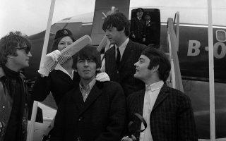 Ο κιθαρίστας των Beatles, Τζορτζ Χάρισον, δέχεται την ιδιαίτερη περιποίηση μίας αεροσυνοδού, η οποία του χτενίζει τα μαλλιά, κατά την έξοδο των «Σκαθαριών» από το αεροπλάνο που τους μετέφερε πίσω στο Λονδίνο, μετά από το σύντομο ταξίδι τους στην Ολλανδία, το 1964. (AP Photo)