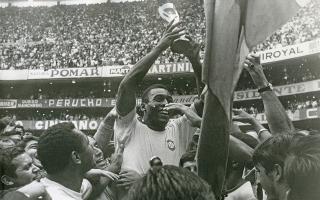 Ο Έντσον Αράντες ντο Νασιμέντο, ευρύτερα γνωστός με το προσωνύμιο Πελέ, σηκώνει στον άερα το τρόπαιο του Παγκοσμίου Κυπέλλου Ποδοσφαίρου, καθώς βρίσκεται περιτριγυρισμένος από ένα τσούρμο Βραζιλιάνων φιλάθλων, λίγο μετά το πέρας του μεγάλου τελικού μεταξύ της Βραζιλίας και της Ιταλίας, στο Στάδιο Αζτέκα, στην Πόλη του Μεξικού, το 1970. (AP Photo/STF)