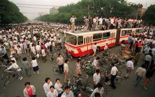 Πλήθος πολιτών έχει συγκεντρωθεί σε μία μεγάλη διασταύρωση του Πεκίνου, όπου οι διαδηλωτές φοιτητές έχουν τοποθετήσει δύο μικρά λεωφορεία ως οδοφράγματα, για να εμποδίσουν την προσέγγιση των δυνάμεων του κινεζικού στρατού στην πλατεία Τιενανμέν, η οποία επί επτά εβδομάδες βρίσκεται υπό κατάληψη από φοιτητές που ζητούν περισσότερη δημοκρατία και μεγαλύτερο σεβασμό των ανθρωπίνων δικαιωμάτων στη Λαϊκή Δημοκρατία της Κίνας, το 1989. (AP Photo/Jeff Widener)
