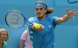 Stefanos Tsitsipas of Greece returns a ball to Kyle Edmund of Britain during their singles match at the Queens Club tennis tournament in London, Thursday, June 20, 2019. (AP Photo/Frank Augstein)