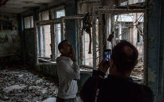 Τουρίστες βγάζουν φωτογραφίες σε εγκαταλελειμμένο σχολείο στην πόλη-φάντασμα Πρίπιατ, στην απαγορευμένη περιοχή του Τσερνόμπιλ. BRYAN DENTON/THE NEW YORK TIMES