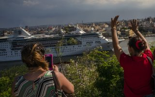 A woman waves goodbye as another takes pictures of the Empress of the Seas, a Royal Caribbean vessel, as it navigates out of the harbor in Havana, Cuba, Wednesday, June 5, 2019. Major cruise lines on Wednesday immediately began dropping stops in Cuba from their itineraries and hastily rerouting ships to other destinations including Mexico, after the Trump administration's new restrictions on travel to Cuba. (AP Photo/Ramon Espinosa)