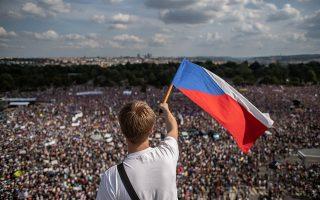 Νεαρός κυματίζει την τσεχική σημαία, καθώς δεκάδες χιλιάδες άτομα συγκεντρώνονται για να διαδηλώσουν κατά του Μπάμπις στην Πράγα.