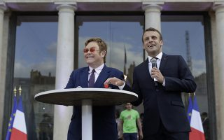 French President Emmanuel Macron, right, and Sir Elton John speak in the courtyard of the presidential Elysee Palace in Paris, Friday, June 21, 2019. Sir Elton John received the Legion of Honor, France's highest award, during a visit to the presidential Elysee Palace (AP Photo/Lewis Joly, Pool)