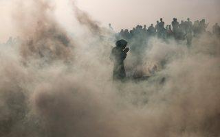 Χιλιάδες Παλαιστίνιες γυναίκες διαδηλώνουν, στην πρώτη μεγάλη πορεία στη Λωρίδα της Γάζας. Μία εξ αυτών διακρίνεται μέσα στους καπνούς των δακρυγόνων. Μάρτιος 2014. SINA PRESS/HEIDI LEVINE