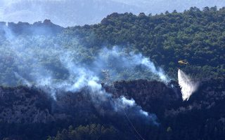 epa07675244 A Fire Brigade helicopter drops water on to the woods, in Alava, northern Spain, 26 June 2019. A fire has been detected in the forest of Sobron, next to Alava, due to high temperatures in the area and several firefighters have been sent there in order to avoid a bigger threat as flames approach a hydroelectric power plant in a dam nearby.  EPA/David Aguilar