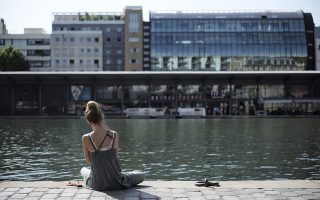 A woman sits under the sun along the Canal de l'Ourcq in Paris, Friday, June 28, 2019. Schools are spraying kids with water and nursing homes are equipping the elderly with hydration sensors as France battles a record-setting heat wave baking much of Europe. (AP Photo/Lewis Joly)