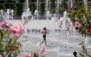 Ενα παιδί αναζητεί δροσιά στο σι-ντριβάνι της πλατείας Σιτροέν, στο Παρίσι.