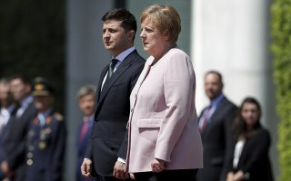 German Chancellor Angela Merkel, right, trembles strong as she and Ukraine's President Volodymyr Zelenskiy, left, attend the national anthems as part of a military welcome ceremony in Berlin, Germany, Tuesday, June 18, 2019. Merkel appeared unwell as she met with Zelenskiy in Berlin, visibly shaking as she received the new Ukrainian president at the chancellery. The incident came Tuesday afternoon as the two stood outside Merkel's office in the hot weather while a military band played their national anthems. Merkel's office had no immediate comment and the two were to hold a press conference later in the afternoon. Following the anthems Merkel seemed better, walking along the red carpet with Zelenskiy into the building, pausing to greet the military band and take a salute. Merkel turns 65 next month. (AP Photo/Michael Sohn)