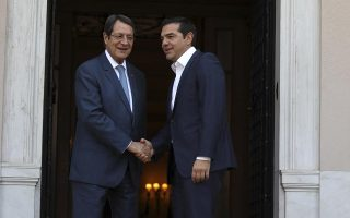 Greece's Prime Minister Alexis Tsipras, right, welcomes the Cypriot President Nicos Anastasiades at Maximos Mansion in Athens, Monday, Sept. 17, 2018. Despite the end of its bailouts, Greece remains under scrutiny from its creditors, who will carry out quarterly reviews. Standard & Poor's has raised Cyprus' credit grade by a notch to BBB-, lifting the country back into investment grade after near-bankruptcy five years ago. (AP Photo/Thanassis Stavrakis)