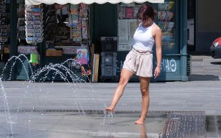 epa07677339 A woman cools off at a fountain in downtown Turin, Italy, 27 June 2019. Temperatures registered 34 degrees Celsius with hot winds and high humidity gripping most of the country.  EPA/ALESSANDRO DI MARCO