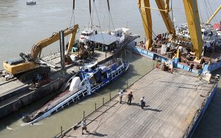 A crane lifts the sightseeing boat out of the Danube river in Budapest, Hungary, Tuesday, June 11, 2019. Eight people are still missing from the May 29 collision between the Hableany (Mermaid) sightseeing boat and the Viking Sigyn river cruise ship at Budapest's Margit Bridge. (AP Photo/Darko Bandic)