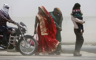 People cover themselves as they walk during a dust storm on a hot day in Prayagraj, India, Sunday, June 16, 2019.  Many parts of India are experiencing extreme heat conditions. (AP Photo/Rajesh Kumar Singh)