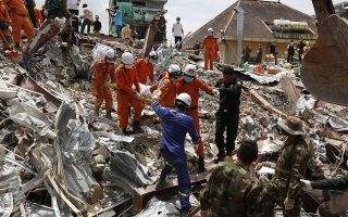 epa07667561 A Cambodian rescue team carries a worker's body at the site of a collapsed building on a construction site in Preah Sihanouk province, Cambodia, 23 June 2019. A new seven-storey building owned by a Chinese company, collapsed in Preah Sihanouk province, killing at least 18 workers and leaving 24 workers injured, according to reports.  EPA/KITH SEREY