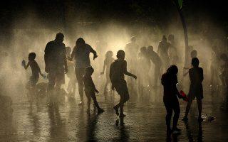 Μικροί και μεγάλοι δροσίζονται στα συντριβάνια του πάρκου Madrid Rio στα περίχωρα της Μαδρίτης