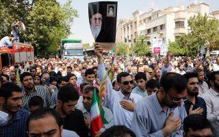 Ιρανοί υψώνουν πορτρέτα του ανώτατου ηγέτη Αγιατολάχ Αλί Χαμενεΐ στη διάρκεια επιμνημόσυνης τελετής για τα θύματα του πολέμου με το Ιράκ.