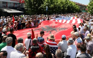 People hold Albanian And U.S. flags during the 20th anniversary of the deployment of NATO Troops in Kosovo in Pristina, Kosovo June 12, 2019. REUTERS/Florion Goga