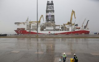 Port workers clean the dock area backdropped by the drilling ship 'Yavuz' scheduled to be dispatched to the Mediterranean, at the port of Dilovasi, outside Istanbul, Thursday, June 20, 2019. Turkish officials say the drillship Yavuz will be dispatched to an area off Cyprus to drill for gas. Another drillship, the Fatih, is now drilling off Cyprus' west coast at a distance of approximately 40 miles in waters where the east Mediterranean island nation has exclusive economic rights. The Cyprus government says Turkey's actions contravene international law and violate Cypriot sovereign rights. (AP Photo/Lefteris Pitarakis)