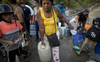 A woman carries a container with water collected from an open pipe above the Guaire River, during rolling blackouts which affects the water pumps in people's homes, offices and stores, in Caracas, Venezuela, Monday, March 11, 2019. The blackout has intensified the toxic political climate, with opposition leader Juan Guaido blaming alleged government corruption and mismanagement and President Nicolas Maduro accusing his U.S.-backed adversary of sabotaging the national grid. (AP Photo/Ariana Cubillos)