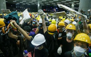 Διαδηλωτές έσπασαν τζαμαρίες του τοπικού κοινοβουλίου και κατάφεραν να το καταλάβουν για αρκετή ώρα. Εγραψαν μάλιστα στους τοίχους συνθήματα όπως «Το Χονγκ Κονγκ δεν είναι Κίνα». REUTERS/ THOMAS PETER