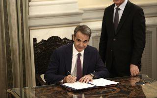 Ο πρωθυπουργός, Κυριάκος Μητσοτάκης, υπογράφει το πρακτικό της ορκωμοσίας της κυβέρνησης.