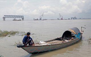 Ψαράς από το Μπανγκλαντές στέκεται δίπλα στην υπό κατασκευήν γέφυρα του ποταμού Πάντμα. Οι φήμες για ανθρωποθυσίες κόστισαν τη ζωή σε οκτώ αθώους.