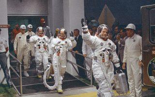Ο κυβερνήτης της διαστημικής αποστολής Απόλλων 11, Νιλ Άρμστρονγκ, χαιρετάει προς τις κάμερες, καθώς κατευθύνεται μαζί με τα άλλα δύο μέλη του πληρώματος της αποστολής, Μάικλ Κόλινς και Μπαζ Όλντριν, στον πύραυλο Saturn V, ο οποίος θα εκτοξευτεί με προορισμό το Σελήνη, στο Διαστημικό Κέντρο Κένεντι στο νησί Μέριτ της Φλόριντα, το 1969. (AP Photo)